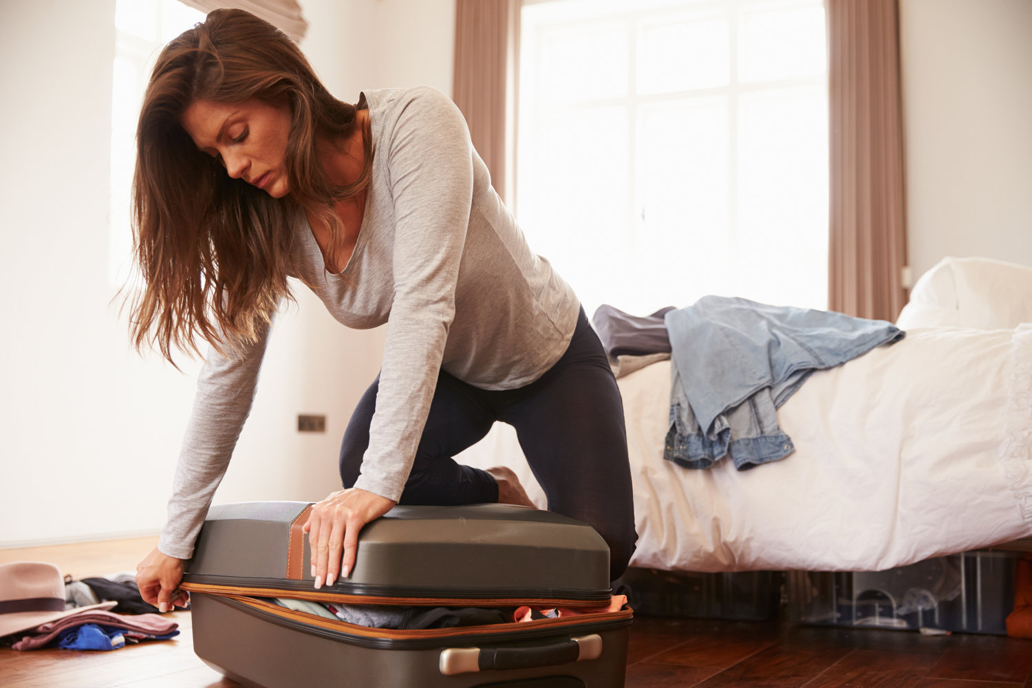 Woman Packing For Vacation Trying To Close Full Suitcase